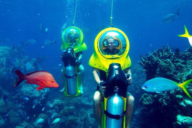 水下摩托艇 完全由您自由操纵的水下摩托艇,可以行驶在水下3米深处,享受这美妙独特的体验。您也不需要成为一个游泳高手或者潜水高手来操纵它,简单得很。 两人一前一后地坐好,肩部以上的位置有个透明的玻璃头罩,可以自由自在地呼吸。在一个完全舒适的环境下,可以观赏海中全景。 为了您的安全,在水下30分钟的摩托艇行驶过程中,会有一个潜水教练一直陪伴在您的左右。 您会穿上我们为您准备的潜水外套,蓝色探险工作人员会花15分钟时间向您讲解操控水下摩托艇的方法以及安全指南和水下交流手势。 水下摩托艇的下沉过程会在一个液压平台